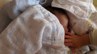 すやすやと眠る娘と、それを触って確かめる娘