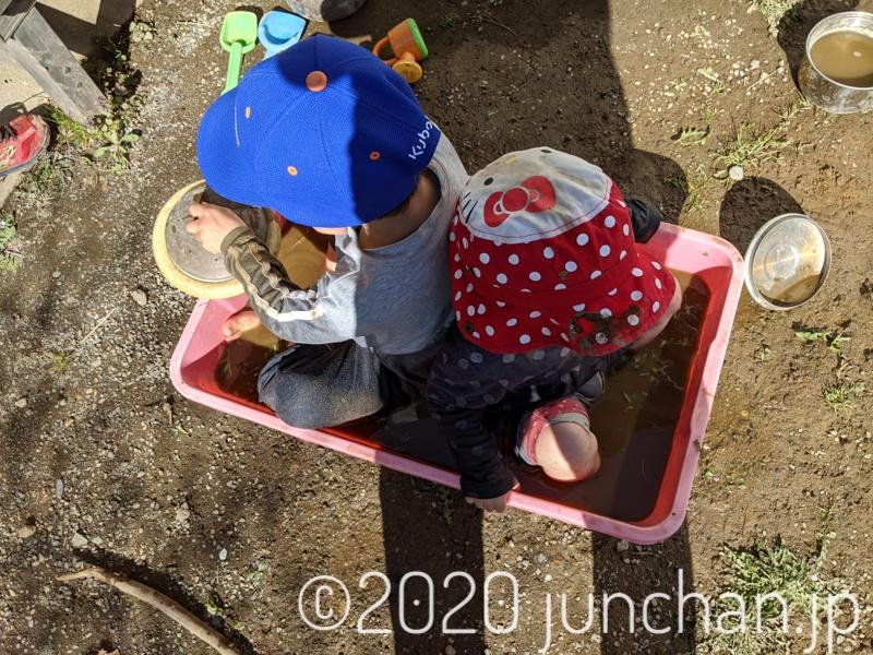 泥水プールで遊ぶ子どもたち