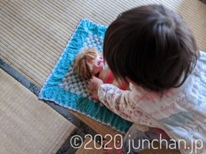 人形を寝かしつける娘