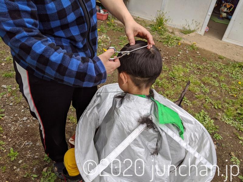 母親に髪を切られている息子