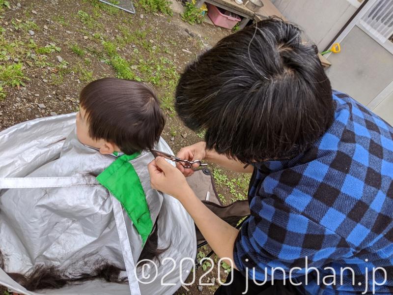 母親に髪を切られている娘