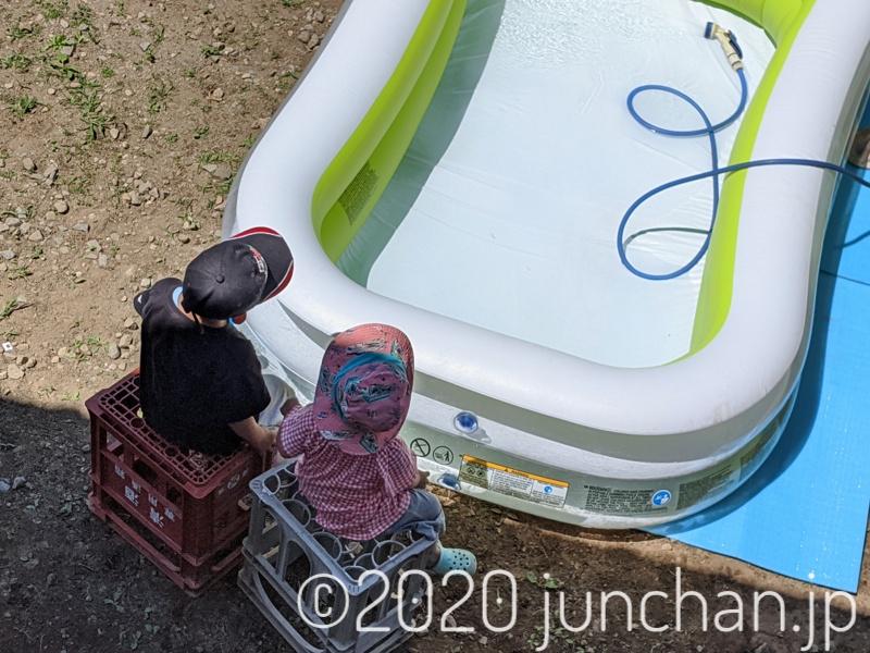 プールの水がたまるのを2人で座って待つ子どもたち