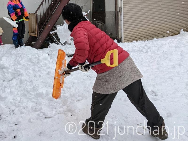 すくってきた雪を雪山に投げつける
